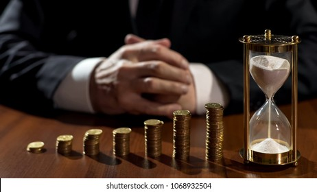 Piles of coins growth, sand flowing in hourglass, businessman waiting for profit