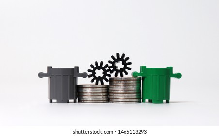 Piles of coins with miniature trash cans and miniature cogwheel. The concept of waste disposal costs.