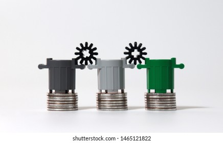 Piles of coins with miniature trash cans and miniature cogwheel.  The concept of the cost of waste disposal.