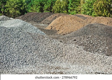 piles of gravel and mixed sand on construction site in forest