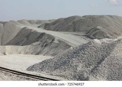 Piles of limestone rocks with the railroad in the foreground. Gravel hills. Mining industry.