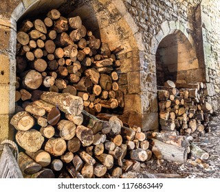 Piles of logs stored in medieval stone alcoves.