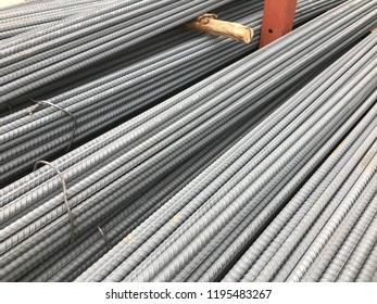 Piles of long cylindrical steel construction rods.