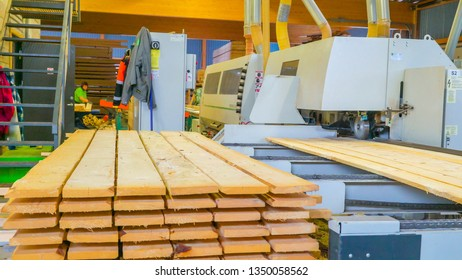 Piles of lumbers lined up to be smoothened by a big machine being controlled by a worker in the sawmill factory