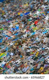 Piles of multi-colored jigsaw pieces that diminish to a soft focus background