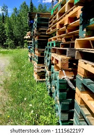 Piles of Multicolored Pallets Stacked in the Green Grass