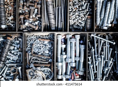 Piles of nuts, bolts, and washers create an industrial themed background. Square containers create a uniform or order amongst the chaos of the metallic supplies.