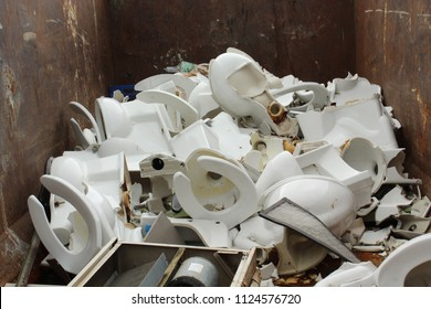 Piles of old white broken ceramic toilets in dumpster trash outside school undergoing a remodeling project.