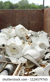 Piles of old white broken ceramic toilets and other debris in dumpster trash outside school undergoing a remodeling project.