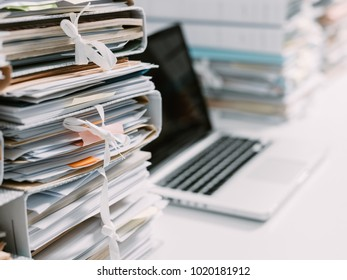 Piles of paperwork in the office and laptop on the desktop
