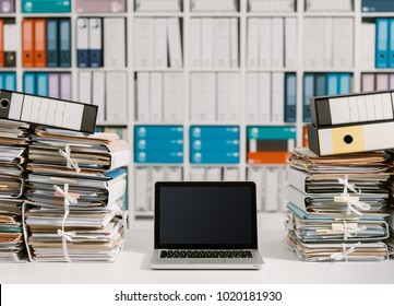 Piles of paperwork in the office and laptop on the desktop - Shutterstock ID 1020181930