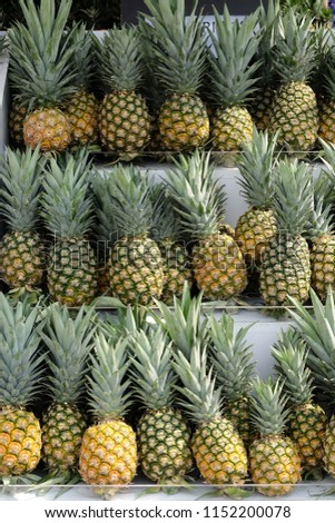 Piles of pineapple on market shelf
