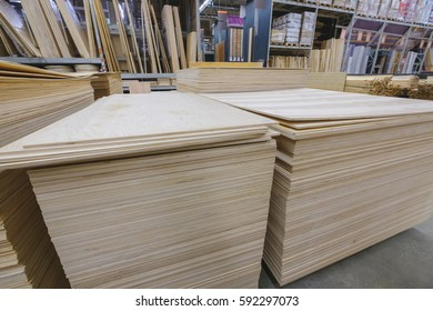 Piles of plywood in different sizes and types on pallets in construction material store storage