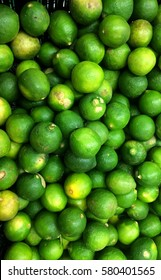 Piles of reshly harvest Calamondin or calamansi lime  ripe  on display for sale.