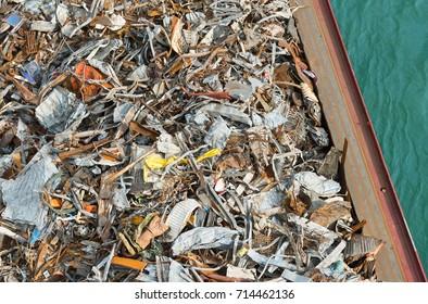 Piles of scrap metal on board of barge