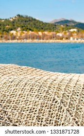 Piles of sea fishing nets, drying in the sunshine and sitting by the quayside in the bay at Port d'Andratx, Mallorca, Spain.