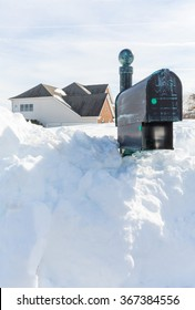 Piles of snow bury the mail box of a modern single family house after blizzard and snow drifts