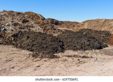Piles of soil deposits at landfill over old dump.