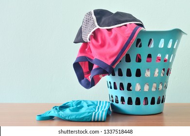 Piles of sport cloths in laundry basket in blue background. Messy, cluttered most active teenager room.