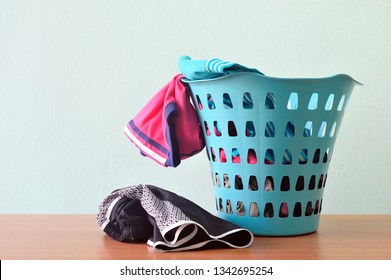 Piles of sport cloths in laundry basket. Messy, cluttered most active teenager room.
