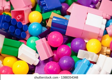 Piles of toys. A lot of colorful toys including balls and plastic construction toys or building blocks, top view. Toy for children to develop creativity. Soft focus on the pink ball in the middle.