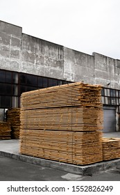 Piles of wooden boards in the sawmill, planking. Warehouse for sawing boards on a sawmill outdoors. Wood timber stack of wooden blanks construction material. Industry.