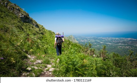 Pilgrim with hat, backpack and stick walking a road between a mountain and a village under the blue sky