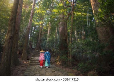 Pilgrim man and woman are hiking up the Daimon-zaka. The route, paved with stone and lined with massive evergreens, leads 600 meters up to the the gates of Nachi Taisha, Wakayama, Japan.