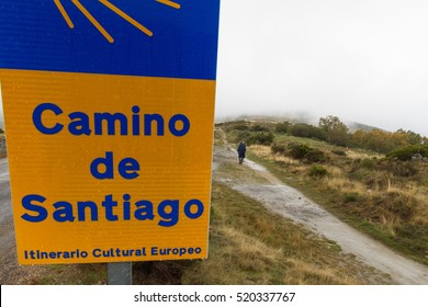 Pilgrim walk on the Camino de Santiago from the. Rain and fog day. With a route indication in the foreground with the inscription: Santiago's road - European Cultural Route