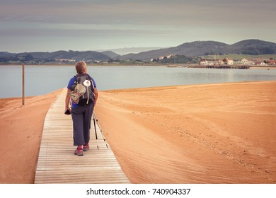 Pilgrim walking to catch the ship that transports you to Santona (Cantabria), way of St. James, Spain