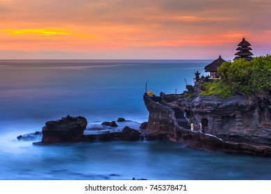 The Pilgrimage Temple of Pura Tanah Lot at sunset, island with an Indonesian shrine on the ocean, long exposure, copy space for text. Tanah Lot Temple, Beraban, Bali, Indonesia.