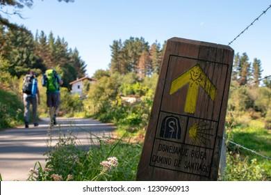 Pilgrims following yellow arrow on Camino Norte, Camino de Santiago in Basque Country.