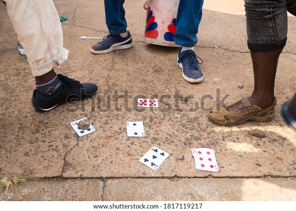 Pilgrims Rest, South Africa - August 06, 2019:  African men playing a game of cards in the street concept daily life in Africa with selective focus on the 2 of spades