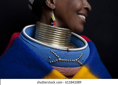 Pilgrims Rest, South Africa - Circa July 2011 - An Ndebele woman smiles as she displays her traditional attire. The neck rings push down on the shoulders to appear like the women have long necks.