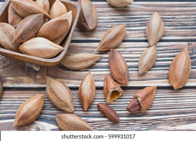 Pili nuts in bowl on wooden background