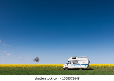 PILICA, POLAND - MAY 1, 2019: Lonely tree and a campervan camper car with background cole colza rapeseed canola with yellow flowers blue sky