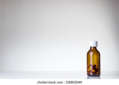 pill bottle with a few pills in the bottle shot in the studio on white perspex background