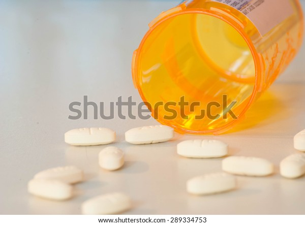 Pill bottle, and medication, on a white countertop.