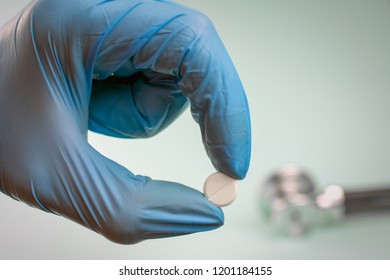 pill with fingers in blue sterilized surgical glove. effective drugs, modern pharmacy  concept.