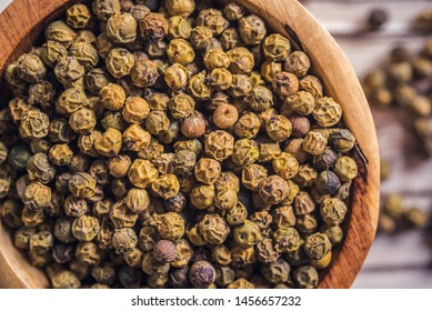 pill green peppercorn on wooden table. top wiew. peppercorn in wood bowl