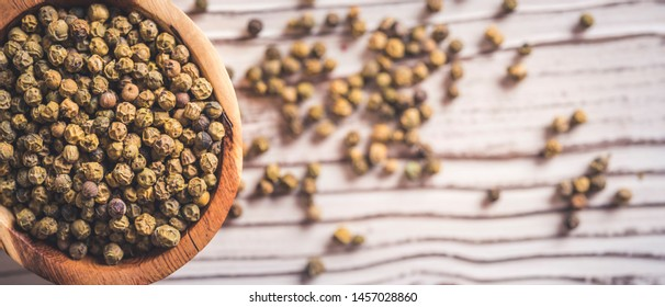 pill green peppercorn on wooden table. top wiew. peppercorn in wood bowl. Panorama