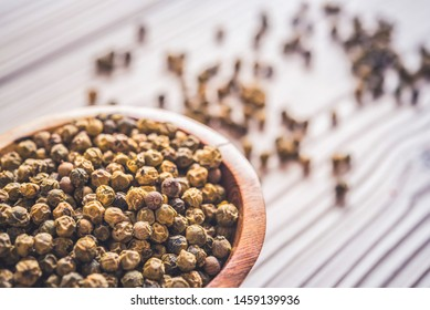 pill green peppercorn on wooden table. peppercorn in wood bowl