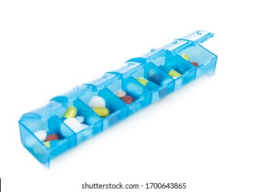 Pill organizer box storing doses of daily medicine on white background