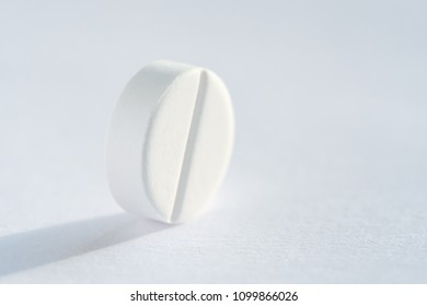 Pill tablet medicine lying isolated on white background extreme close-up macro.