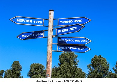 pillar with directions and signs to cities: Berlin, Tokyo, Moscow, Vladivostok, Beijing, Ulan Bator and distance in kilometers