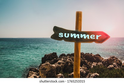 Pillar with a pointer to the beach and the text summer on the background of the sea,