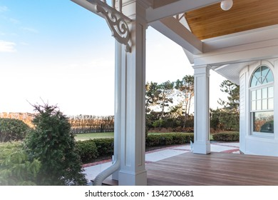 Pillars, millwork, and front window overlooking patio and deck of house with a view of blue skies
