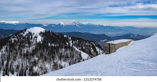 Pillbox (a part of Rupnik defense line) on the Top of the Ratitovec mountain overlooking the Kosmati vrh and Kamnik-Savinja Alps on a winter day