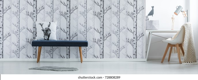 Pillow with deer head drawing on stool against forest wallpaper in room with chair at desk