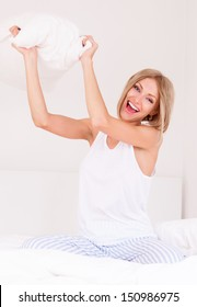 pillow fight, beautiful young woman throwing a pillow at us in bed at home